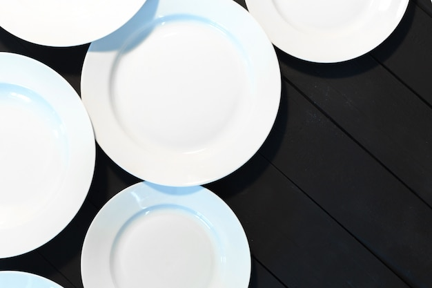 Assiettes blanches vides sur une table en bois