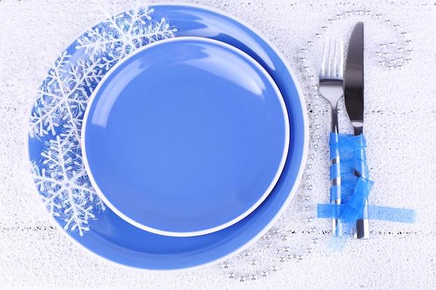 Assiettes bleues, couteau, fourchette, serviette et décoration de noël sur fond de bois