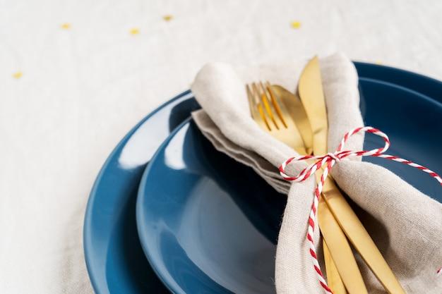 Assiettes bleues et couverts dorés dans une serviette