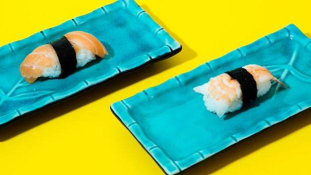 Assiettes bleues avec sushi sur fond jaune