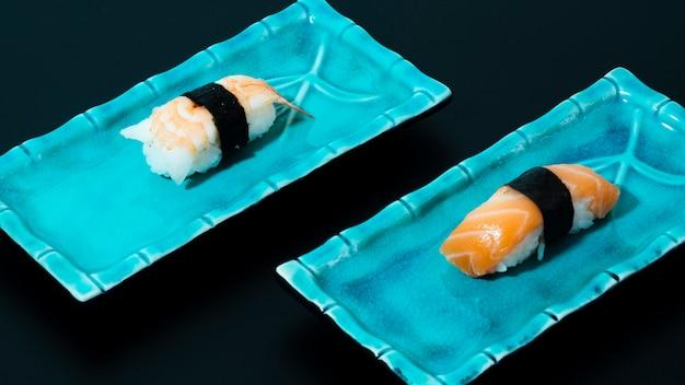 Assiettes bleues avec sushi sur fond noir