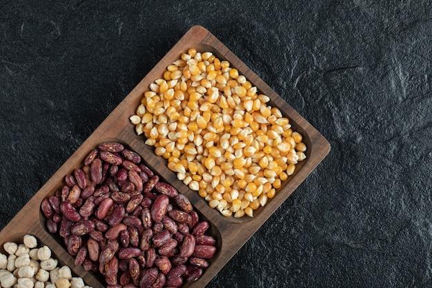 Assiettes en bois avec des haricots crus et du maïs soufflé sur fond noir.