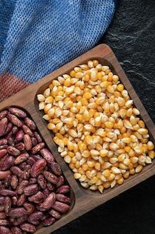 Assiettes en bois avec haricots crus et pop-corn sur un fond sombre