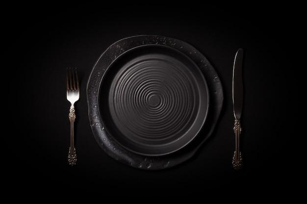 Assiettes en céramique noires rondes vides et couverts vintage
