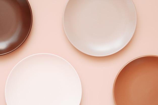 Assiettes en céramique vides de différentes couleurs sur fond corail pastel branché. vue de dessus, écran plat, espace de copie