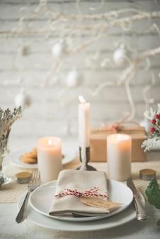 Assiettes et couverts installés sur la table pour le dîner de noël