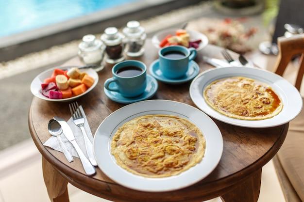 Assiettes avec des crêpes à la banane, des fruits tropicaux et deux tasses de café sur une table en bois.