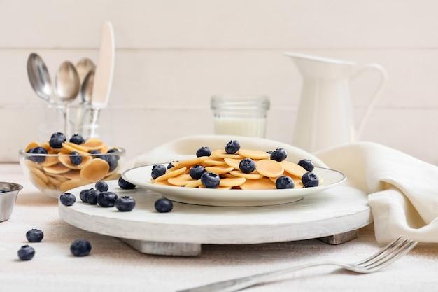Assiettes de crêpes savoureuses aux myrtilles fraîches sur une surface légère