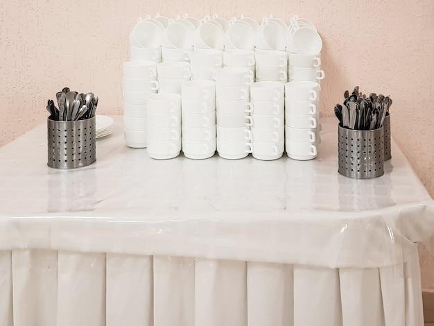 Assiettes creuses blanches et vides dans une pile et couverts sur la table, service au café de l'hôtel