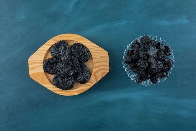 Assiettes de délicieuses prunes séchées placées sur table bleue.