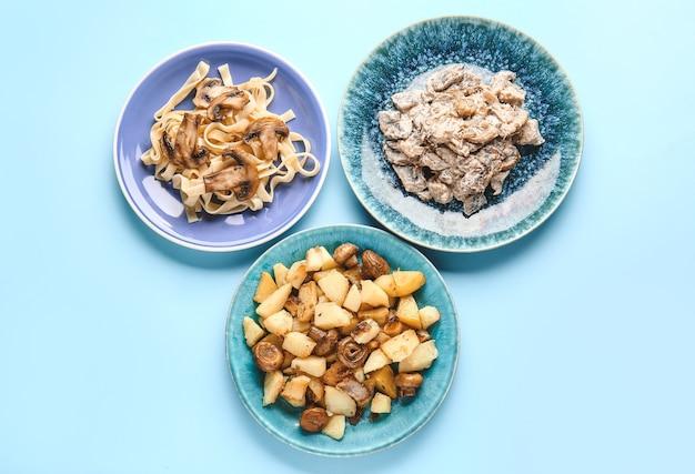 Assiettes avec différents plats de champignons sur fond de couleur