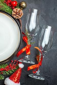 Assiettes à dîner accessoires de décoration branches de sapin chaussette xsmas gobelets en verre arbre de noël sur table sombre