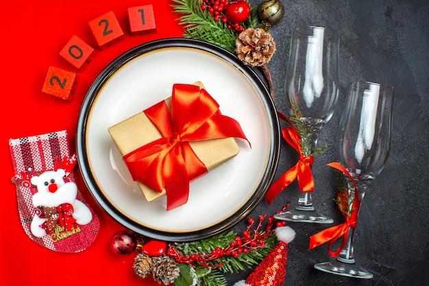 Assiettes à dîner accessoires de décoration branches de sapin numéros de chaussette de noël sur une serviette rouge et gobelets en verre sur fond sombre