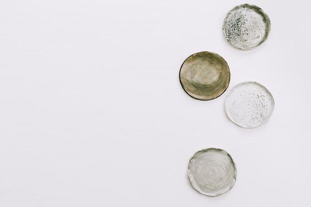 Assiettes faites à la main sur fond blanc. mise à plat, vue de dessus