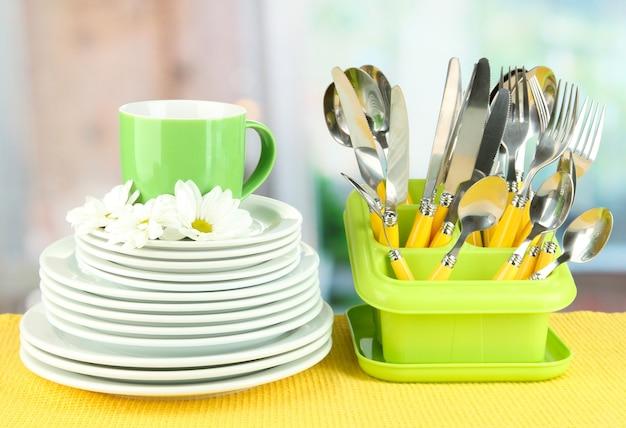 Assiettes, fourchettes, couteaux, cuillères et autres ustensiles de cuisine sur serviette de couleur