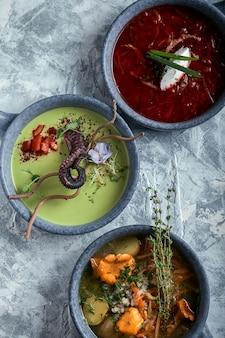 Assiettes grises avec différentes soupes sur un gris.