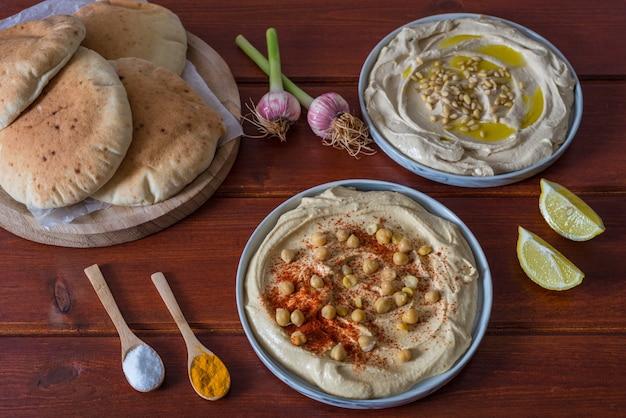 Assiettes de houmous avec du pain pita sur fond rouge en bois