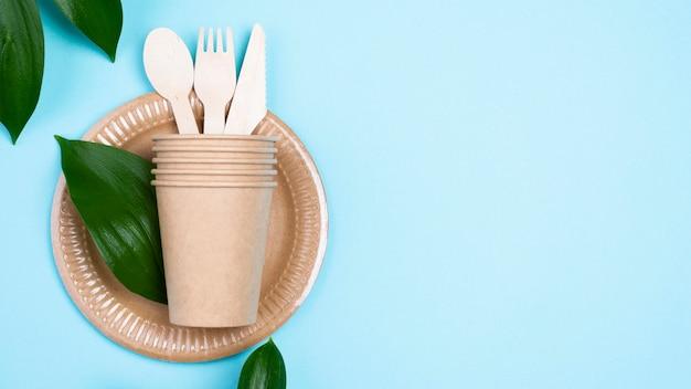 Assiettes jetables avec tasses et couverts fond bleu espace copie