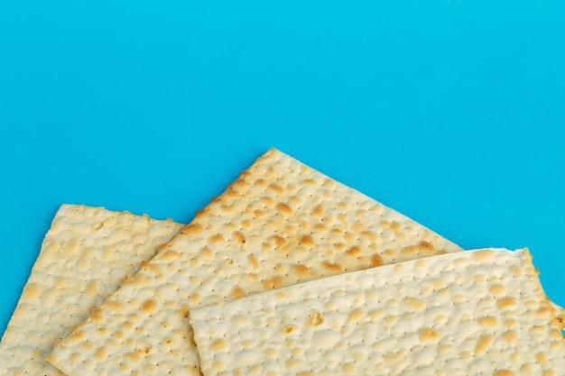 Assiettes de matzo disposées dans n'importe quelle forme sur une surface bleue