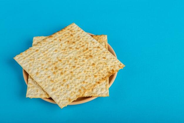 Assiettes de matzo disposées sous la forme d'une étoile de david sur une surface bleue