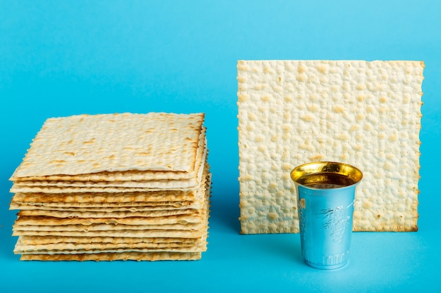 Assiettes de matzo posées les unes sur les autres sur une surface bleue et un verre de vin pour kiddouch