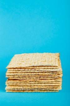Assiettes de matzo posées les unes sur les autres sur une surface bleue