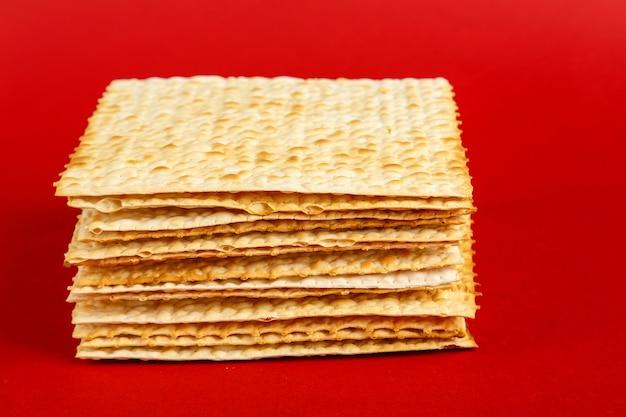 Assiettes de matzo posées les unes sur les autres sur une surface rouge