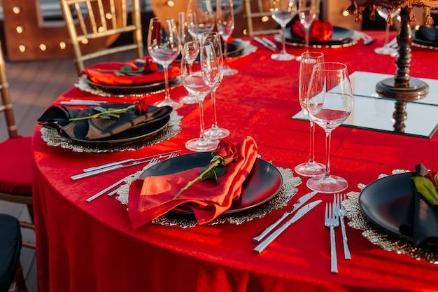 Assiettes de nappe de décor d'arrangement de dîner élégant avec des serviettes et des couverts de verres de roses fraîches