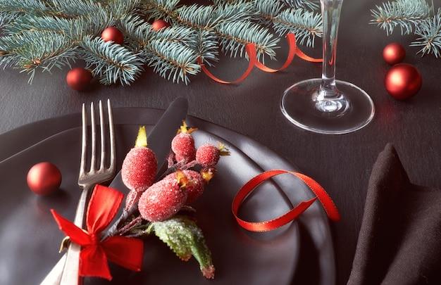 Assiettes noires et couverts vintage avec décorations de noël