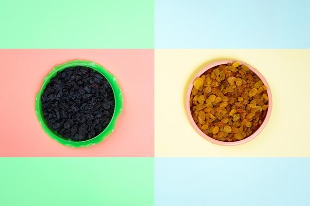 Assiettes en plastique avec des raisins secs jaunes et noirs sur un fond isolé jaune-rose.