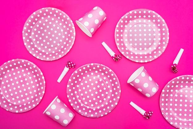 Assiettes en pointillés et sifflets et tasses sur fond rose