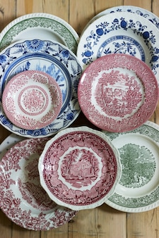 Assiettes en porcelaine vintage de différentes tailles et couleurs sur une table en bois. style rustique.