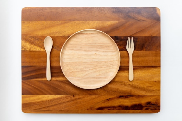 Assiettes rondes en bois d'hévéa aux couleurs naturelles, polies et laquées, placées sur un hachoir en bois d'acacia