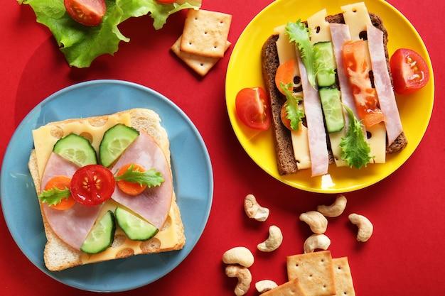 Assiettes avec des sandwichs créatifs sur fond rouge