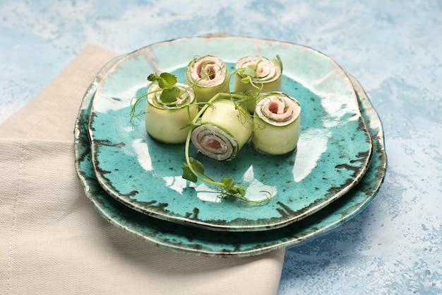 Assiettes avec de savoureux rouleaux de concombre sur la couleur