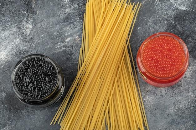 Assiettes en verre pleines de caviar rouge et noir sur une table en marbre.
