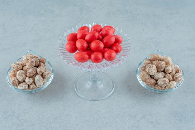 Assiettes en verre pleines de délicieux pain d'épice et de bonbons sucrés rouges sur une surface blanche