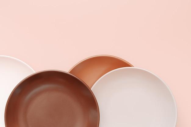 Assiettes vides de différentes nuances sur fond corail pastel branché. vue de dessus, pose à plat, espace de copie