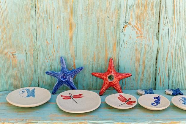 Assiettes vides avec étoiles de mer et poissons en céramique comme décoration de table, design marin