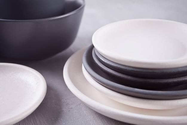 Assiettes vides en noir et blanc sur une table grise.