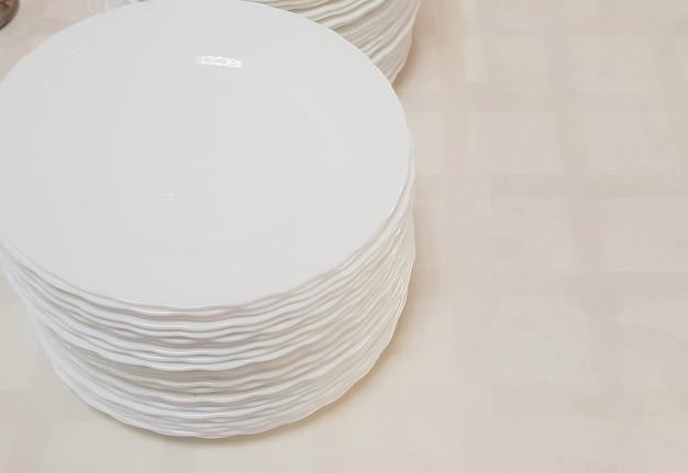 Assiettes vides propres et blanches dans une pile sur la table, service au café de l'hôtel