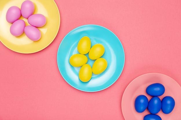 Assiettes vue de dessus avec des œufs colorés