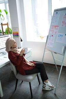 Assis dans un fauteuil. enseignant musulman assis dans un fauteuil buvant du thé et regardant un tableau blanc
