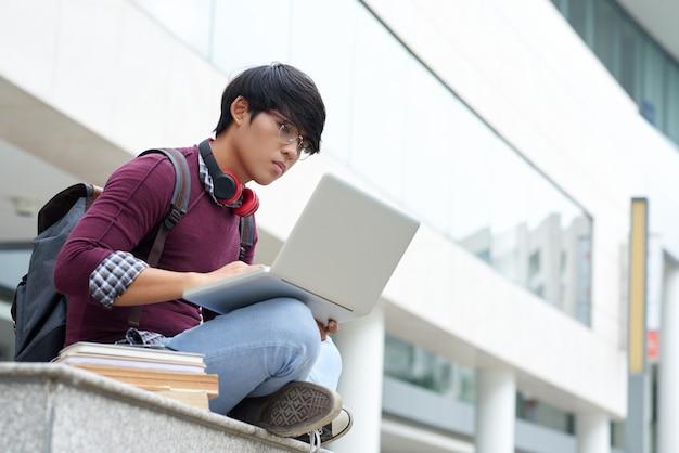 Assis à l'extérieur avec un ordinateur portable