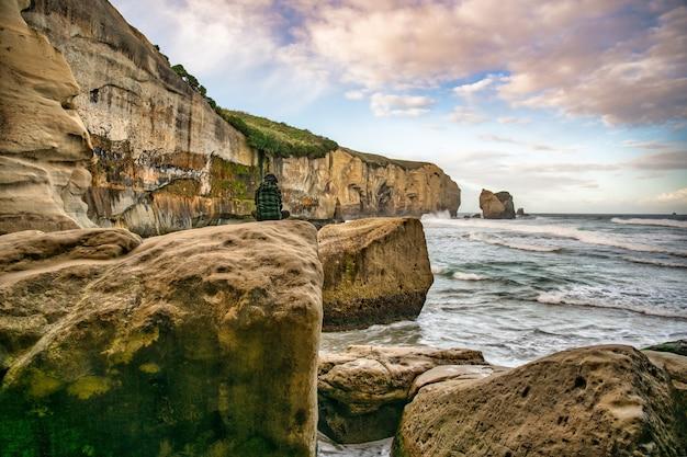 Assis sur un gros rocher sous la falaise abrupte du littoral de la plage du tunnel à regarder le monde passer