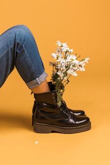 Assis jambes féminines en bottes avec des fleurs à l'intérieur