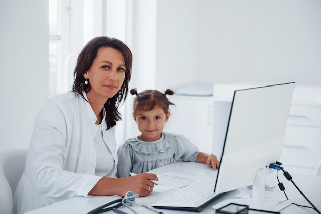 Assis près de la table. un jeune pédiatre travaille avec une petite visiteuse à la clinique.
