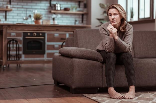 Assis et réfléchi. femme déprimée aux cheveux blonds se sentant triste en étant assise sur un canapé et en pensant
