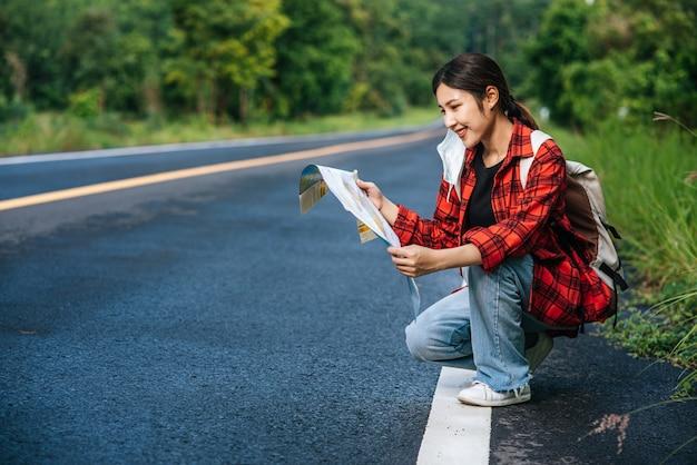 Assis et regardant la carte sur la route.