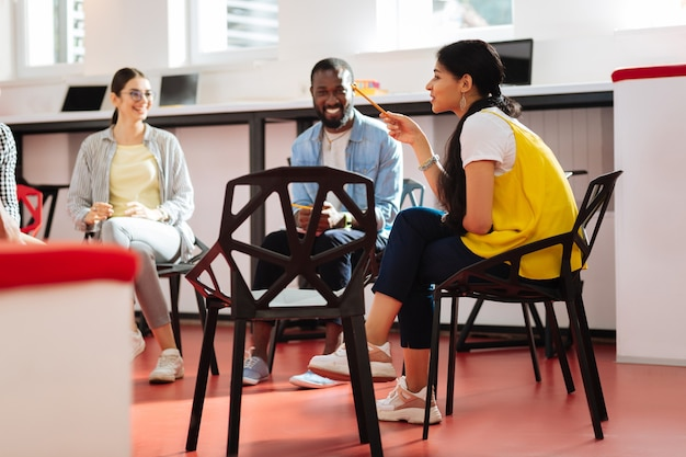 Assis et souriant. des gens joyeux et paisibles assis en cercle et ayant une conversation agréable sur des sujets psychologiques